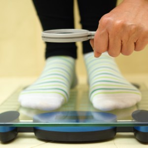 woman feet on weighing scales looking weight over magnifying