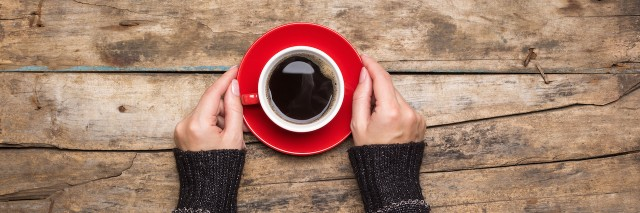 Female hands holding red cup of coffee