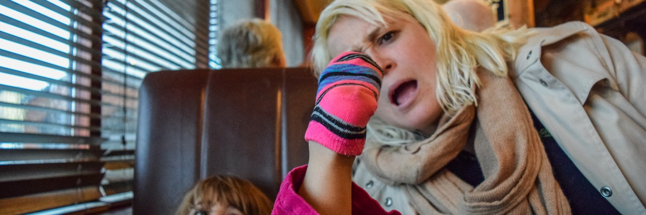 Little girl puts her socked foot on the table at a restaurant, her mother looks on