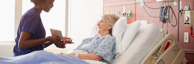 hospital nurse talks to patient in hospital bed