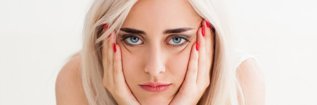 woman who looks annoyed, her hands on her cheeks