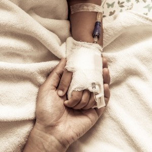 mother holding child's hand who have IV solution in the hospital in vintage color tone