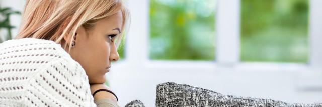 Thinking sad young woman lying on sofa