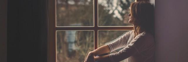 Woman sitting on a windowsill, looking outside