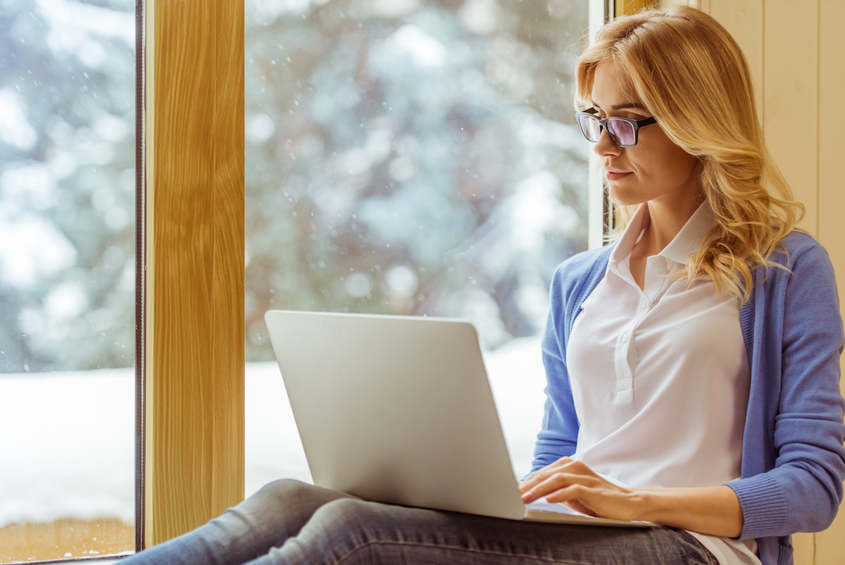 young woman in eyeglasses using a laptop while sitting on the window sill