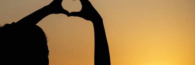 silhouette woman making heart shape with sunset