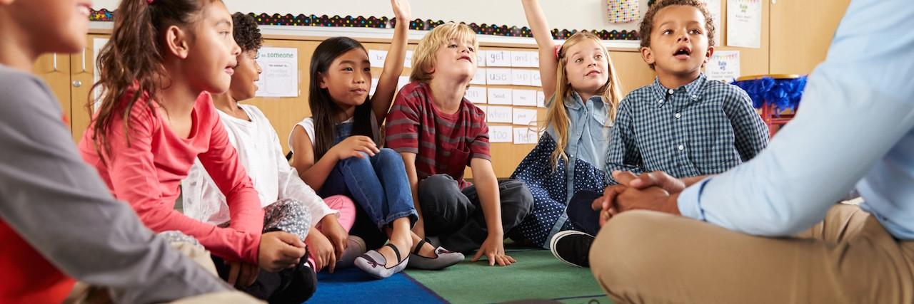 Elementary school kids and teacher sit on floor