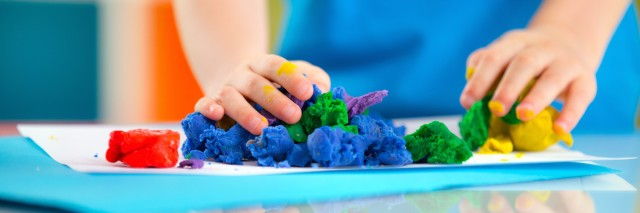 Child playing with colorful dough on table