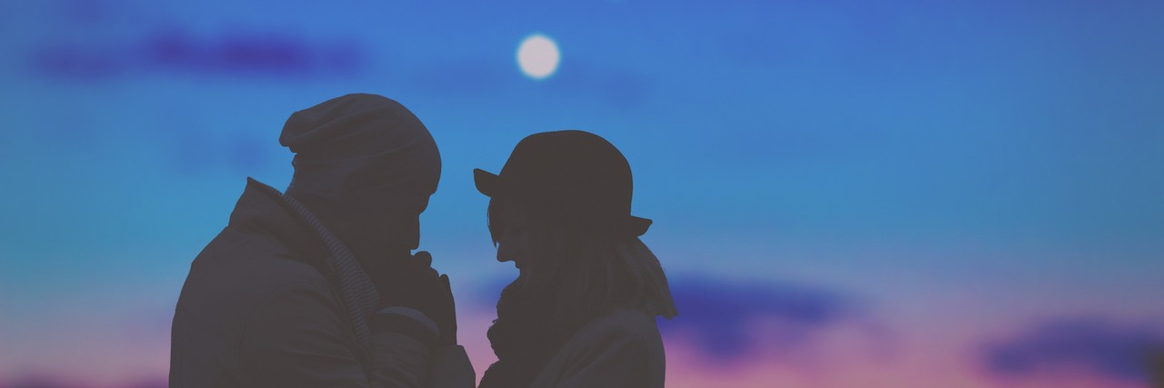Silhouette of couple in front of evening sky