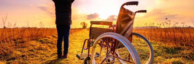 Miracle recovery: young girl gets up from wheelchair and raises hands up. Overjoyed young girl standing up from a wheelchair outdoors. Shot in meadow. Recovery concept