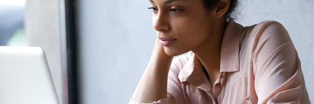 Woman at desk, looking at laptop