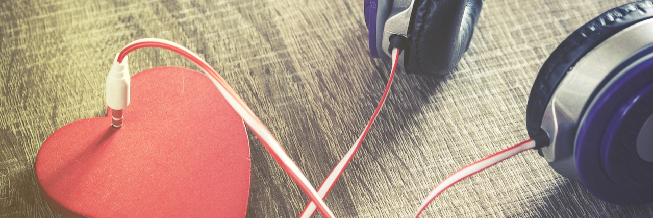 """headphones. The cord is """"plugged into"""" a heart"""