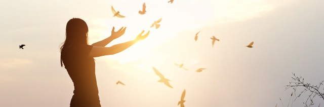 Woman raises hands as birds fly away