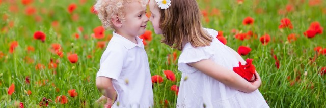 Little curly blond boy and girl play in poppy flower field.
