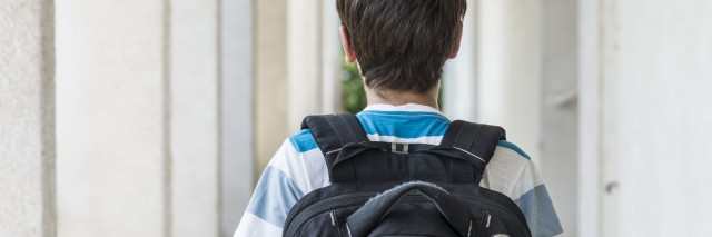 Teenage school boy with a backpack walking to school