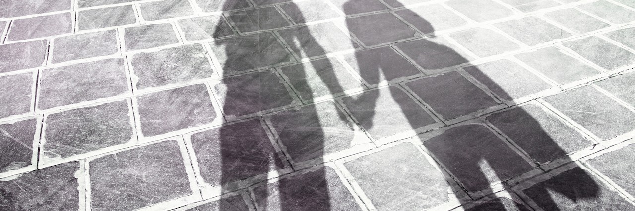 shadows of two people holding hands