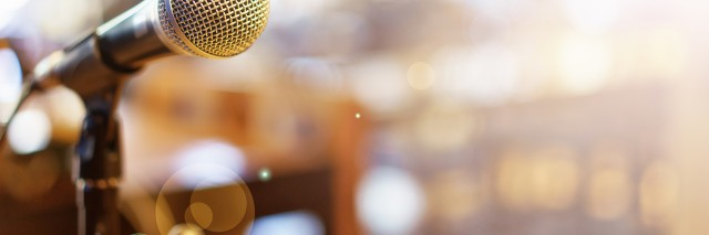 Microphone over a blurred photo of a conference hall