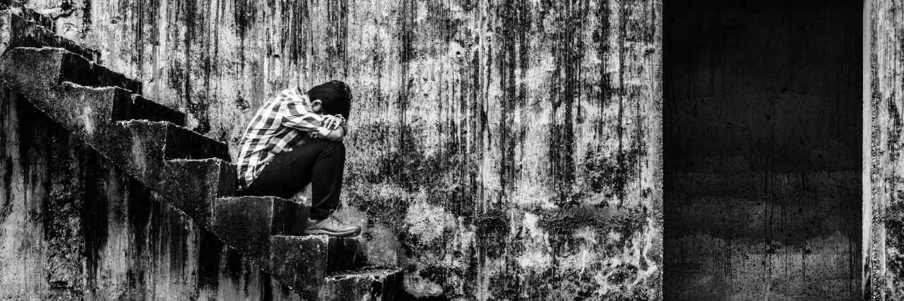 depressed teenager sitting on stair in creepy abandoned building, darkness concept