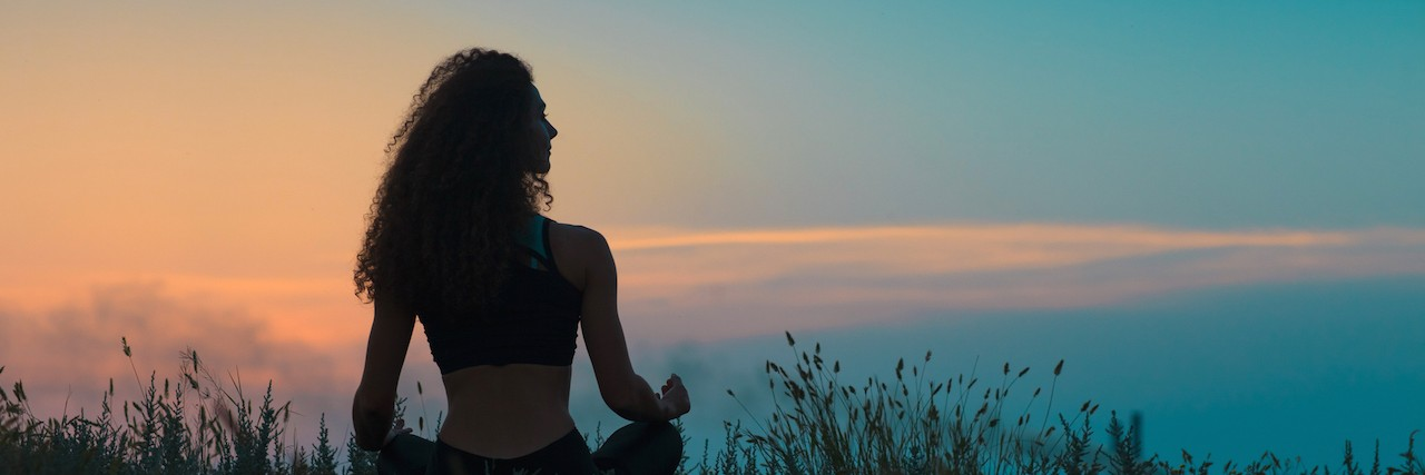 Silhouette of young woman sitting on grass at sunset