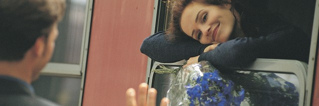a man waving goodbye to a woman, who's smiling on a train