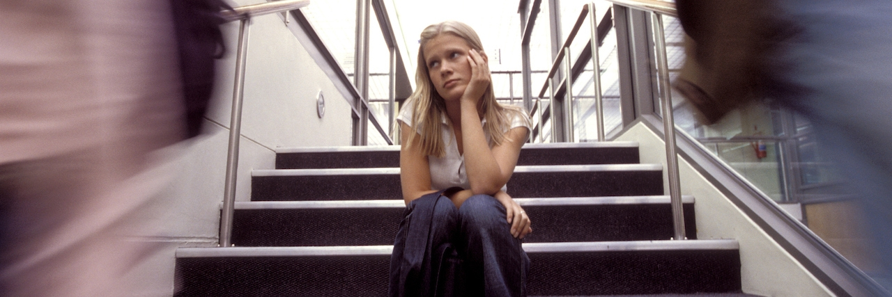 student sitting in a stairwell of a school
