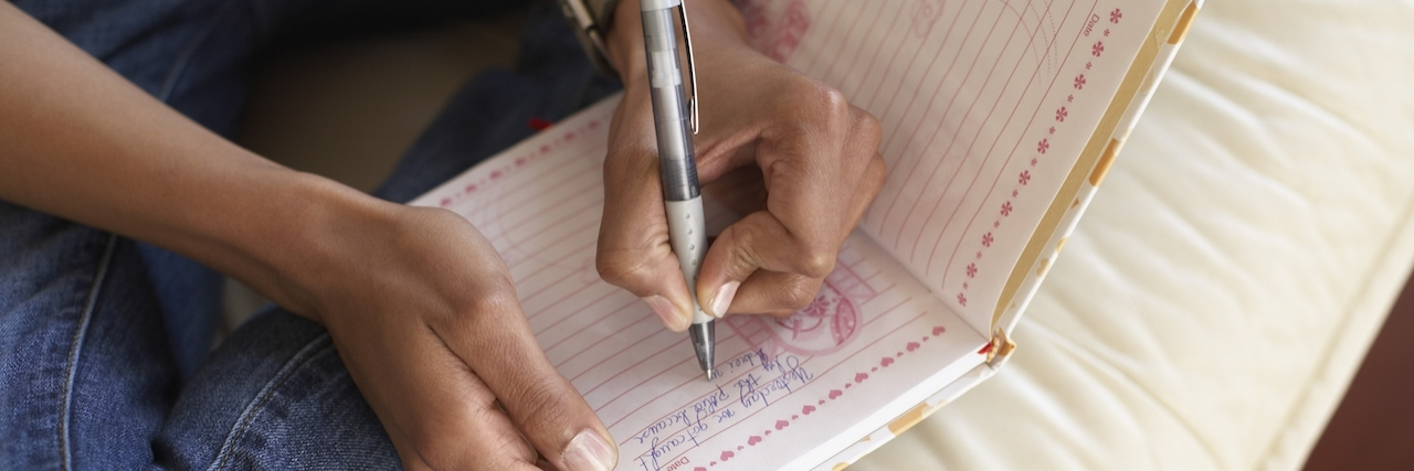 Woman's hands writing in journal