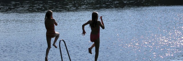 Girls jumping from pier into lake.