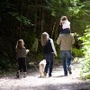 Family walking down road through forest