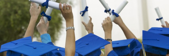 graduates holding diplomas in the air