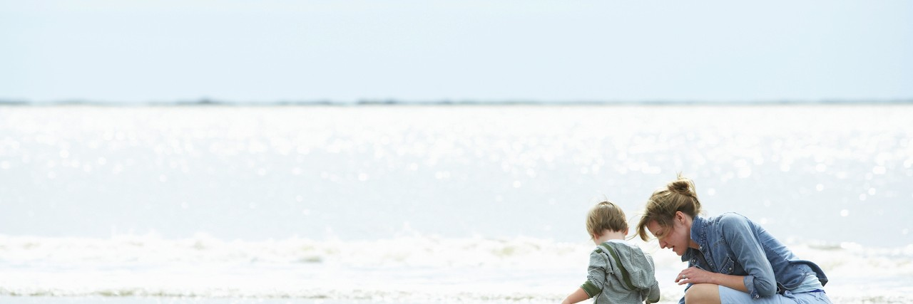 Mother and son playing on the shore of a beach