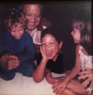 An old photo of the author, his brother, his sister and his grandfather laughing.
