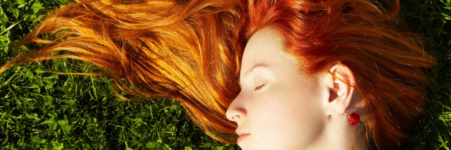 Up close shot of woman with red hair lying on the grass