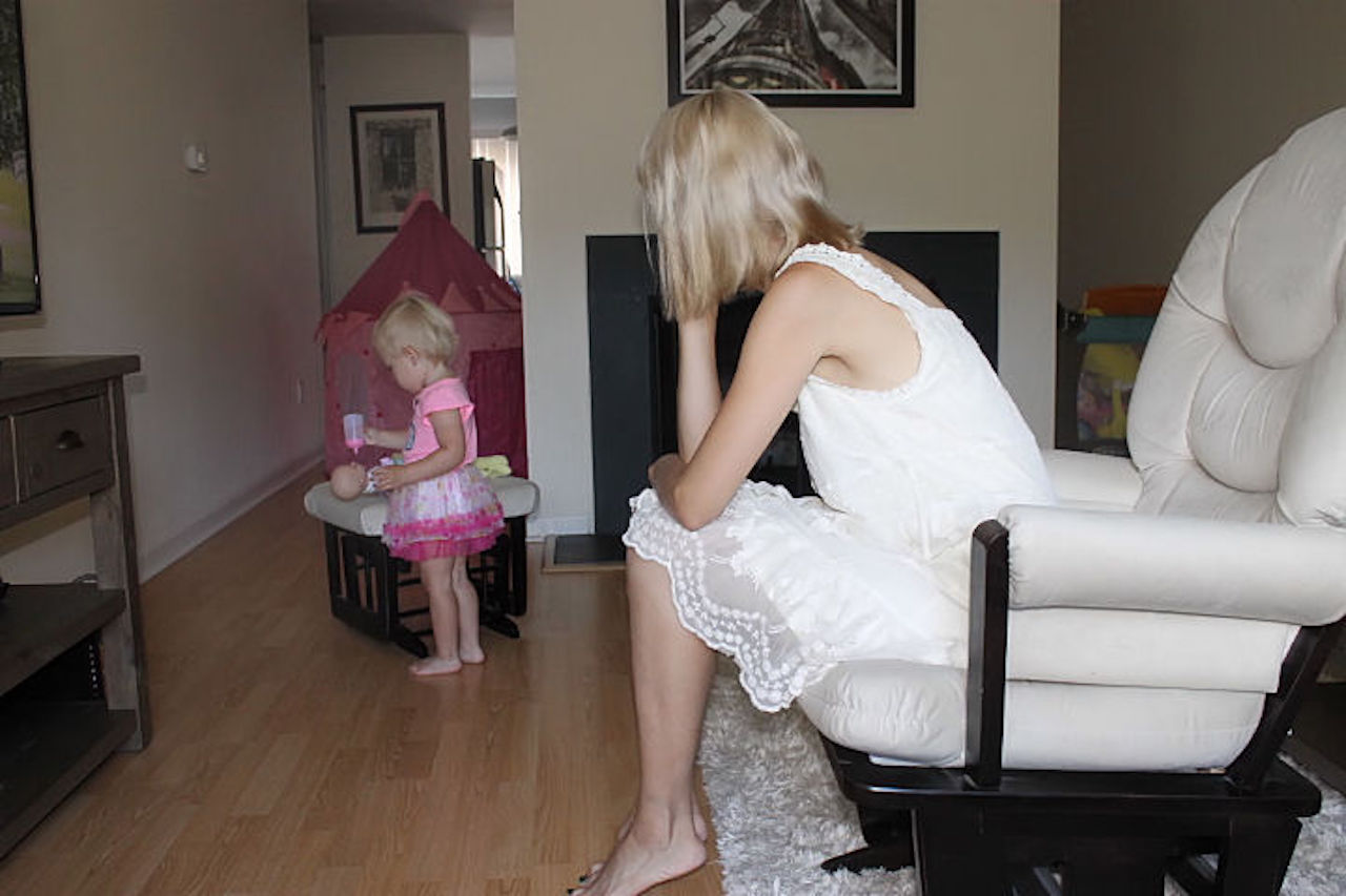mom watching daughter play with doll