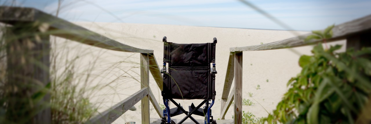 Wheelchair on a beach boardwalk with steps.
