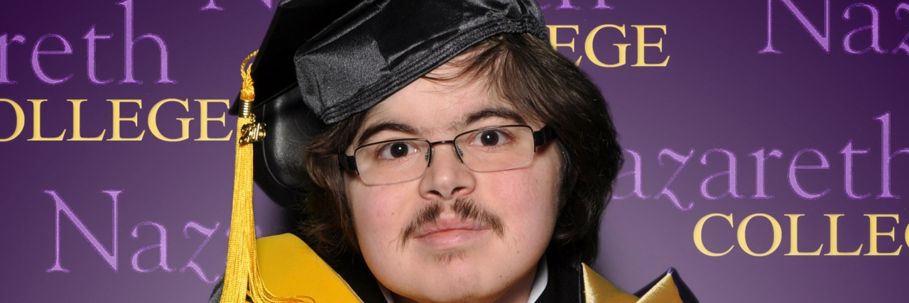 Jonathan graduating from college with his degree in hand