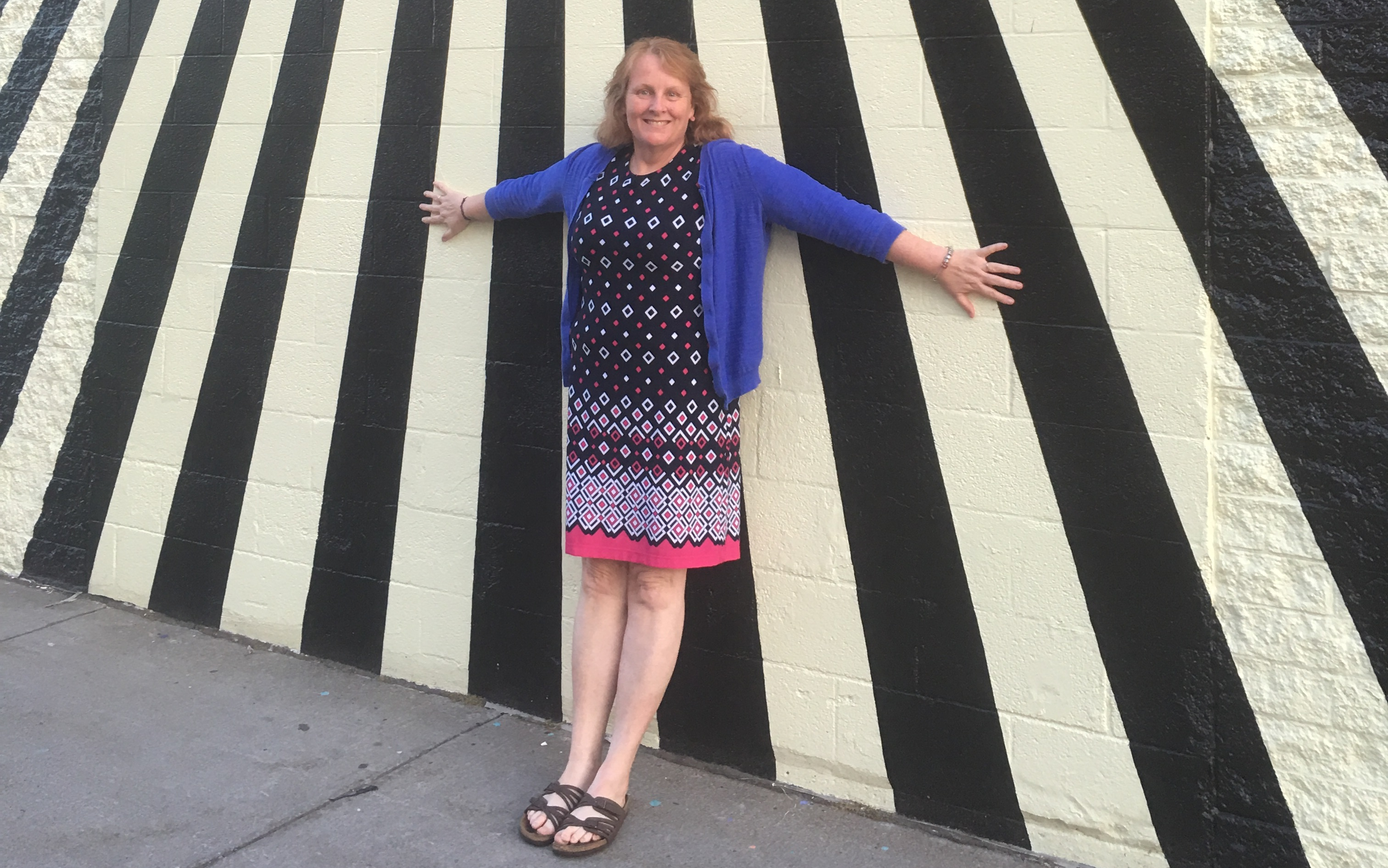 The author standing in front of a black and white striped wall