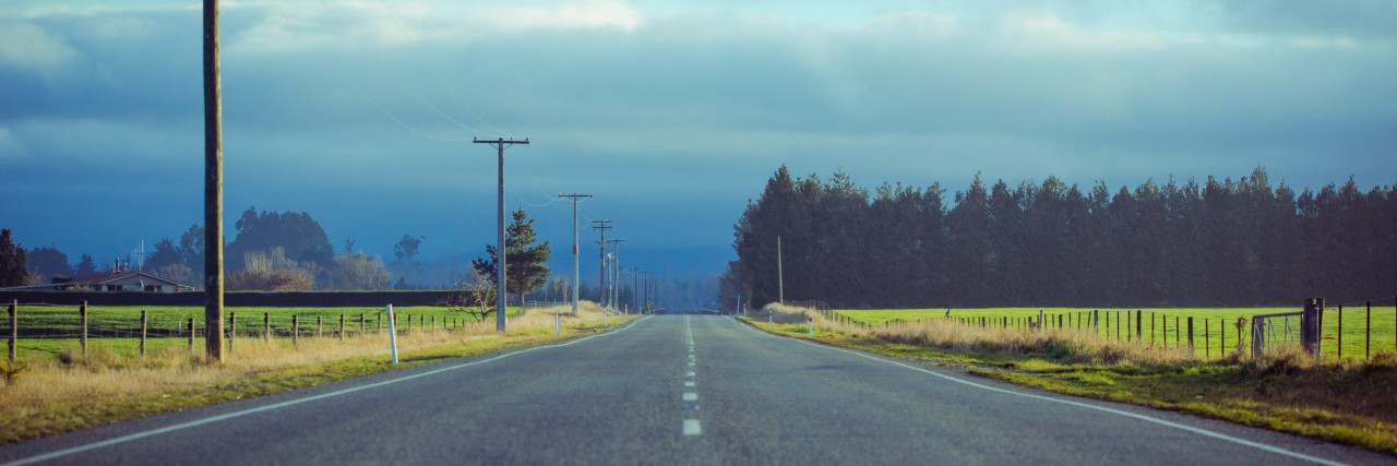 a road with a cloudy sky in the distance, stretching through fields