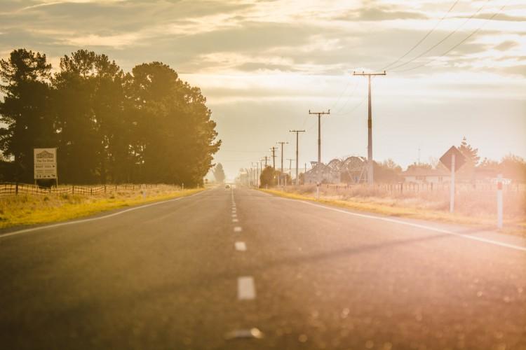 a road going through farmland at sunrise
