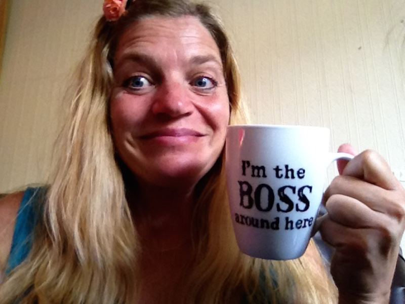 woman holding mug that says I'm the boss around here