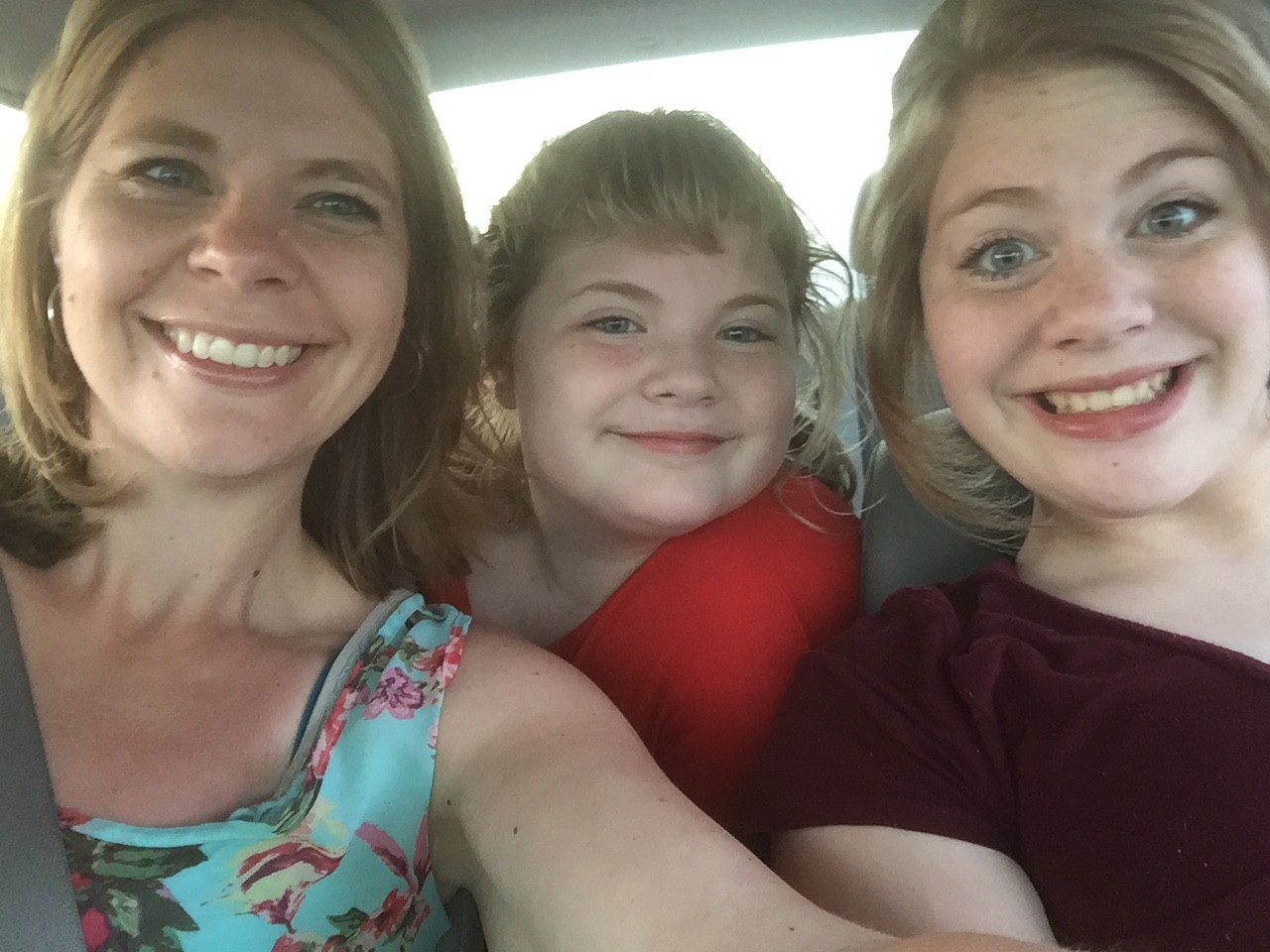 mom and two daughters in the car