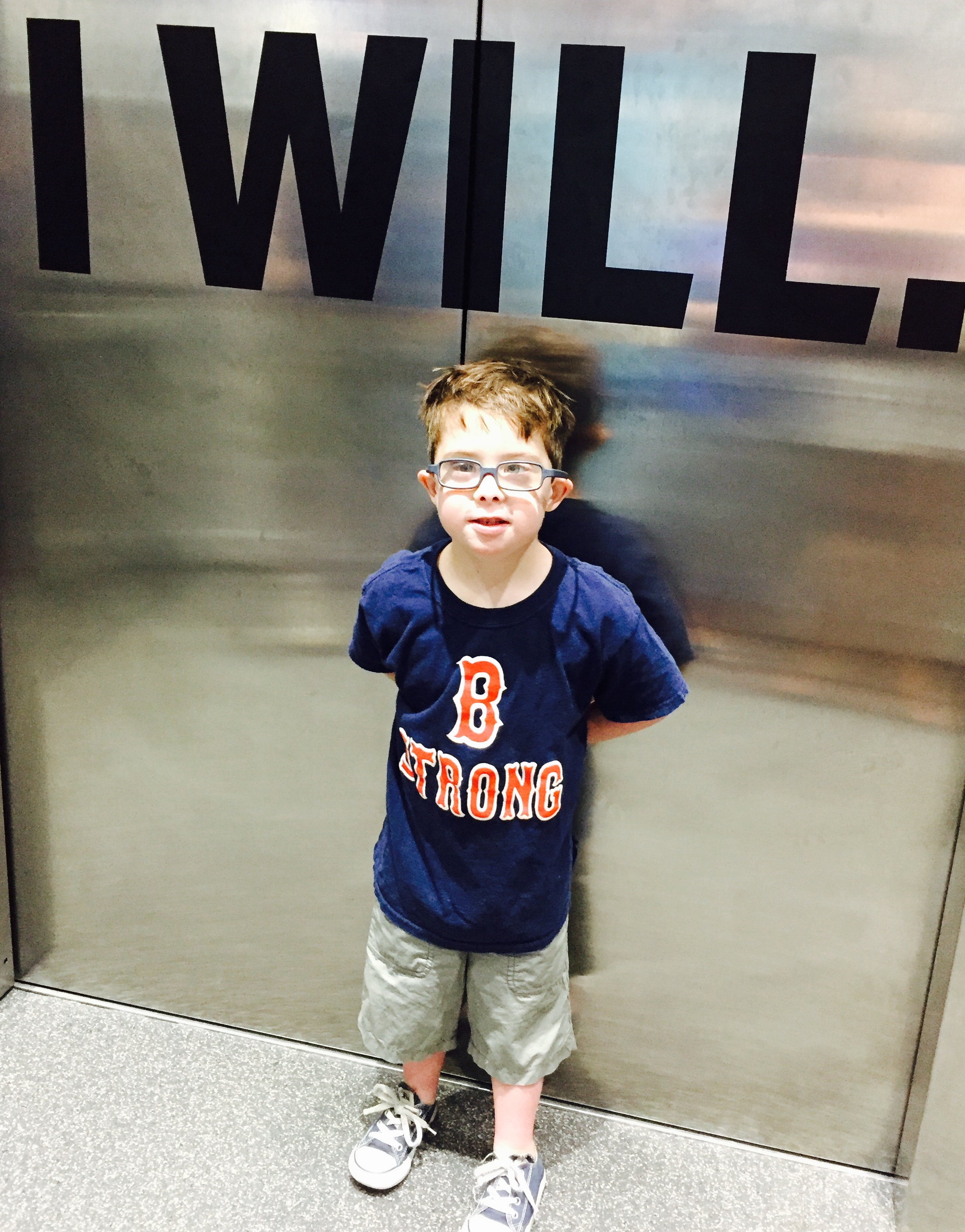 "The author's son standing in front of a mirrored wall that says ""I Will"""