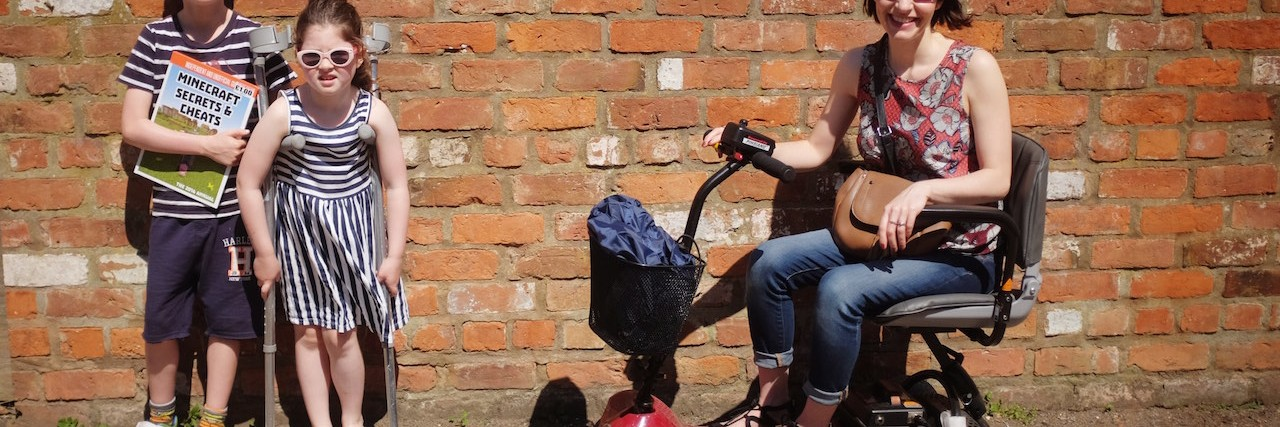 woman sitting on scooter next to two young kids