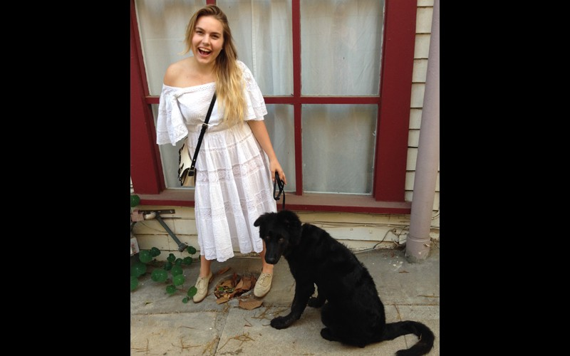 woman wearing white dress with black service dog