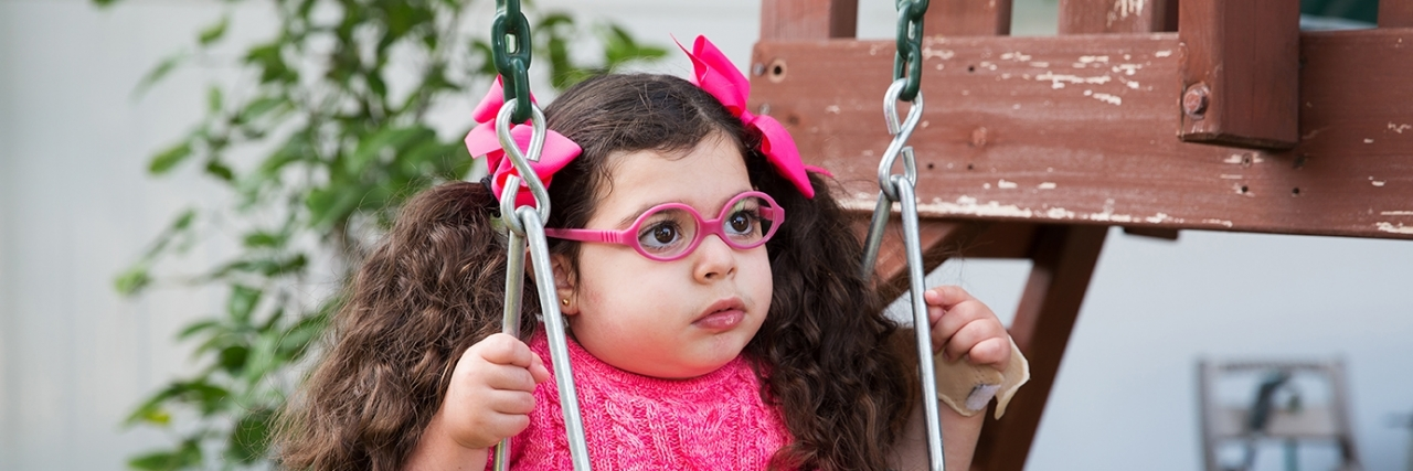 Madison in a swing wearing glasses, a little girl with a rare disease