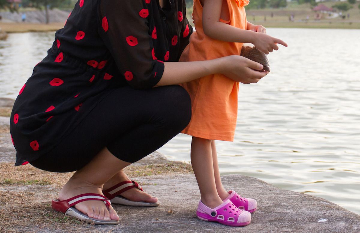 mom crouching down with daughter at water edge