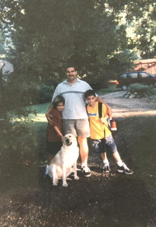 An old picture of the author, her father and her brother outside with their dog.