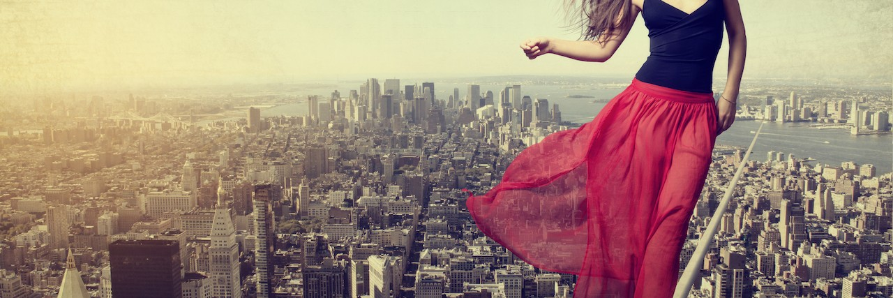 Woman walking on a balance beam over a cityscape