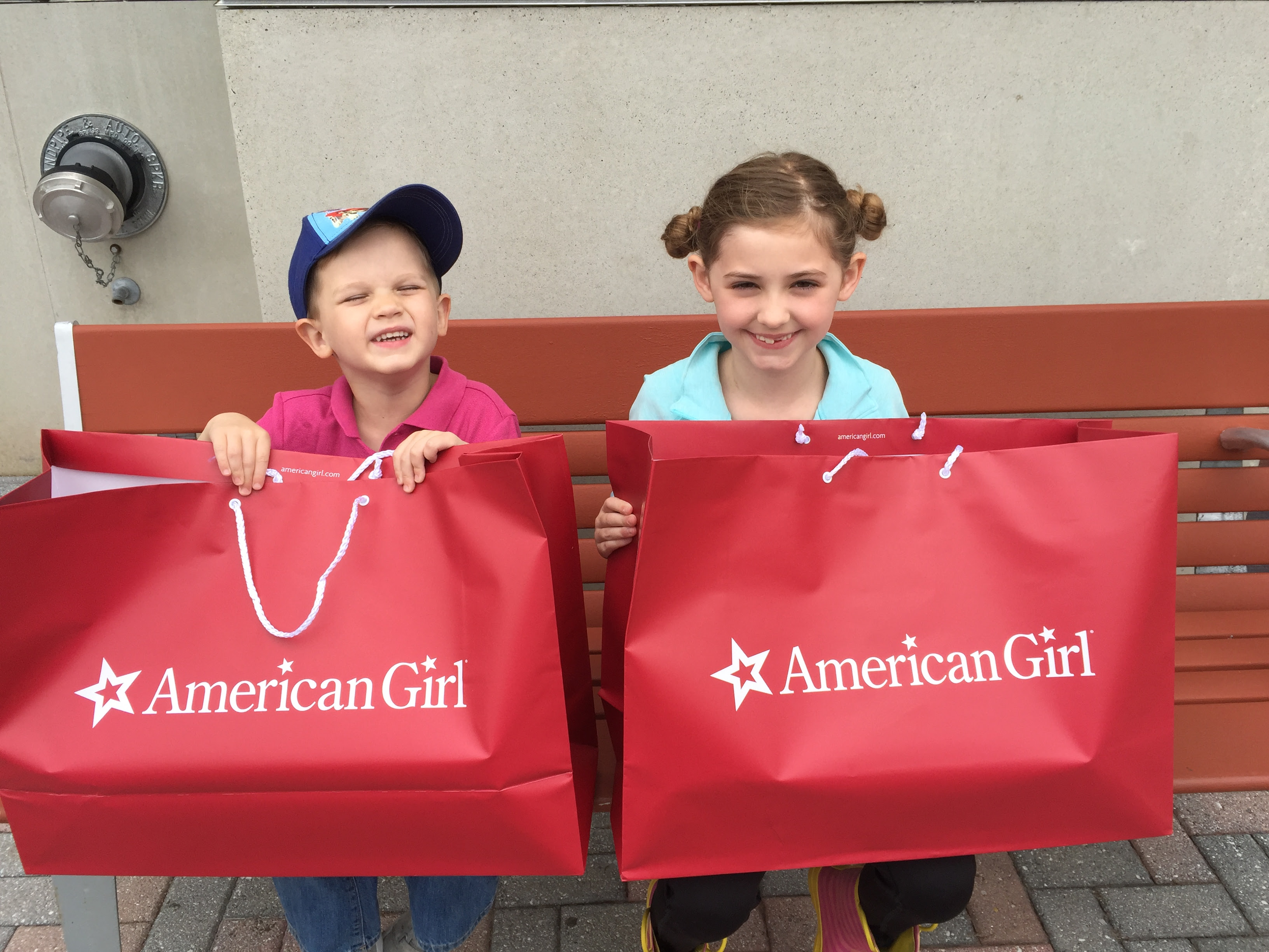 brother and sister with american girl doll bags