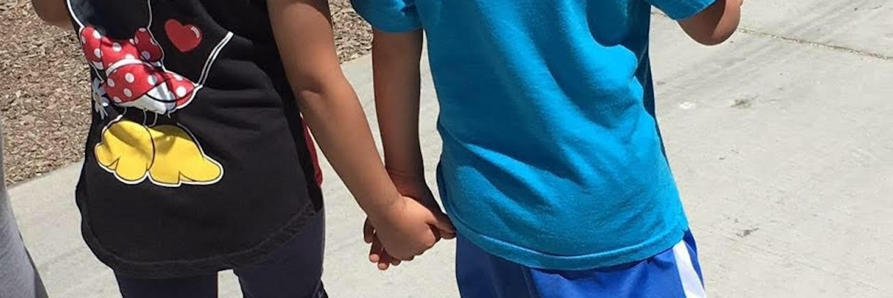sister and brother holding hands