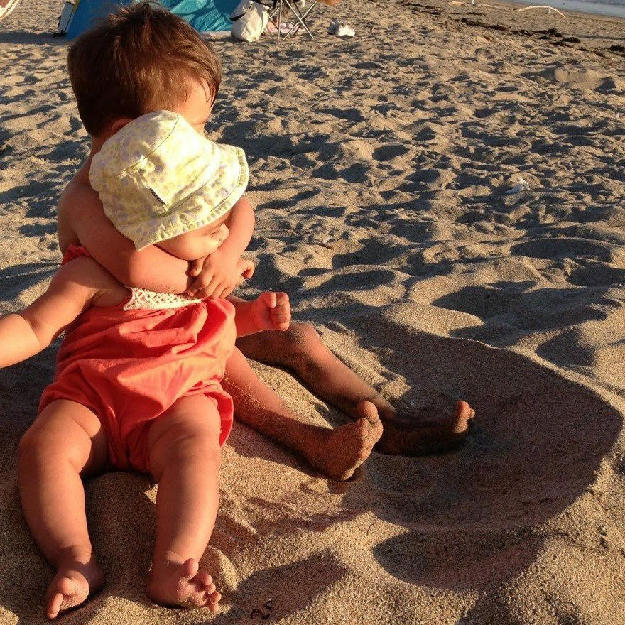 brother hugging baby sister on the beach